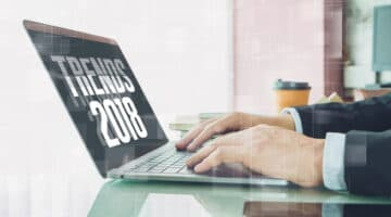 """Hand of Businessman typing """" trends 2018"""" on laptop screen with smartphone and coffee cup in home office or co working space.Concept of workplace using mobile technology."""
